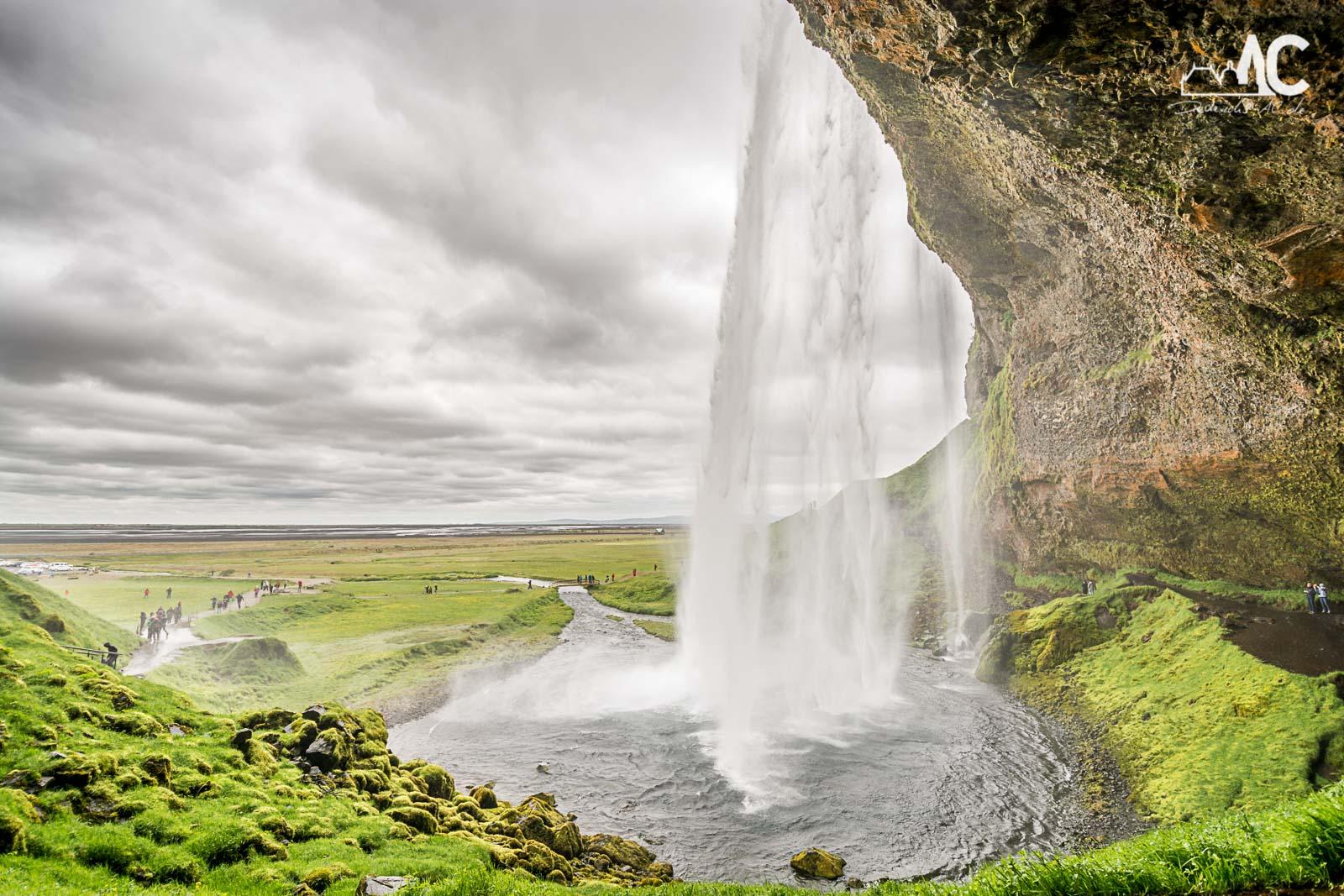 Besucher können hinter den Seljalandsfoss gehen.